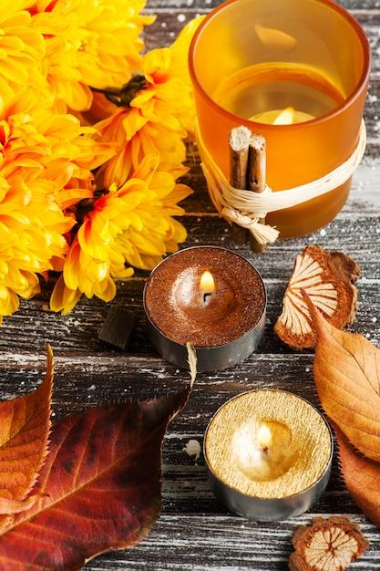 Crisantemo giallo, candele e foglie dorate accese Foto Premium