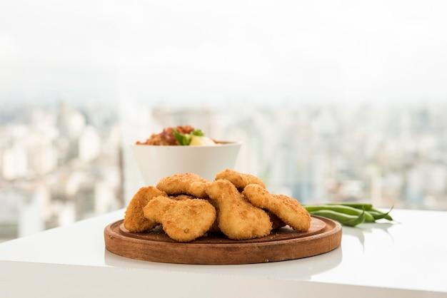Crocchette di pollo croccanti servite sul piatto di legno Foto Gratuite