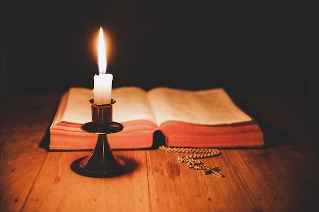 Croce con la bibbia e la candela su un vecchio tavolo di legno di quercia. bellissimo sfondo oro Foto Gratuite