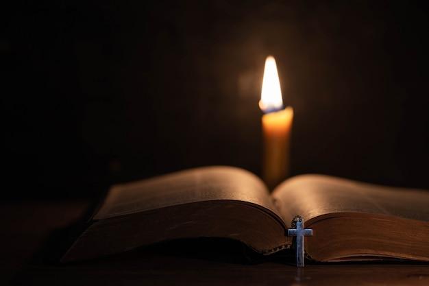 Croce con la bibbia e la candela su un vecchio tavolo di legno di quercia. Foto Gratuite