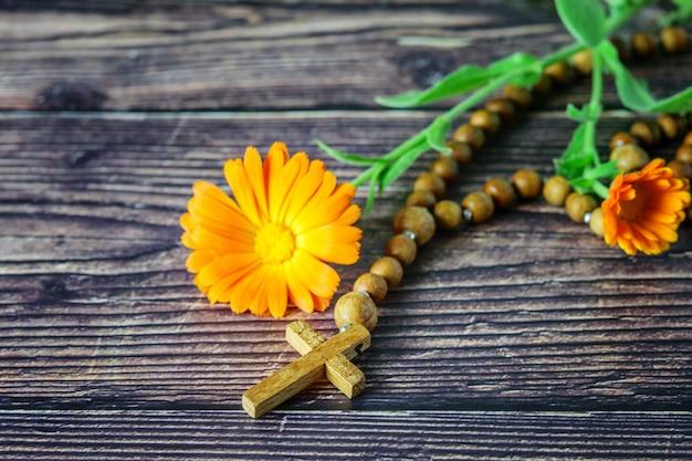 Croce cristiana in legno con coroncina e un fiore su legno scuro Foto Premium