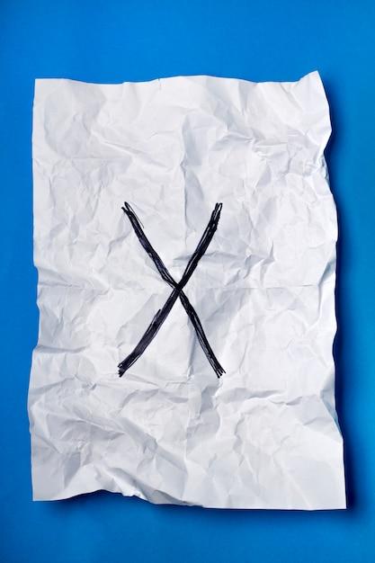 Croce nera su un pezzo di carta bianca stropicciata su uno sfondo blu. Foto Premium