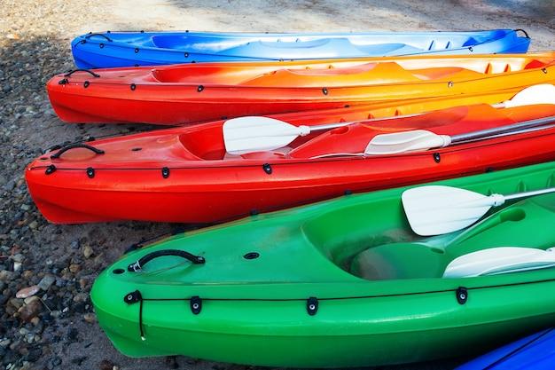 Crogioli di canoa variopinti sulla spiaggia, vista del primo piano Foto Premium