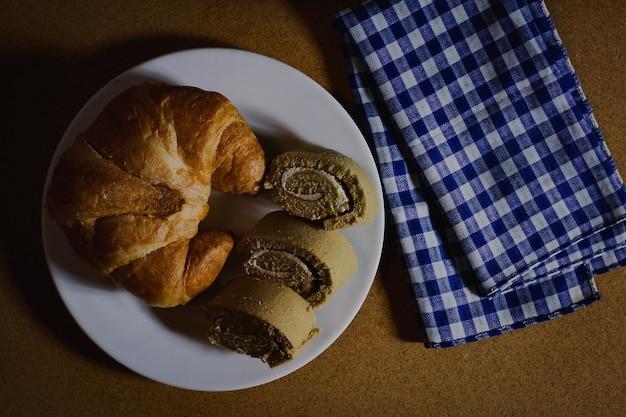 Croissant con rotolo di marmellata sul piatto bianco Foto Premium