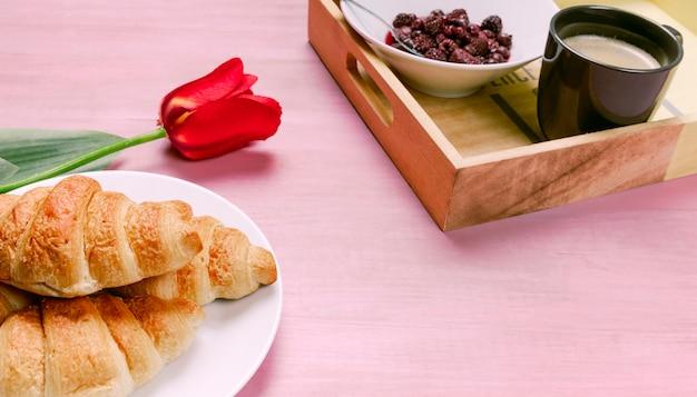 Croissant con tulipano rosso e vassoio con frutti di bosco Foto Gratuite