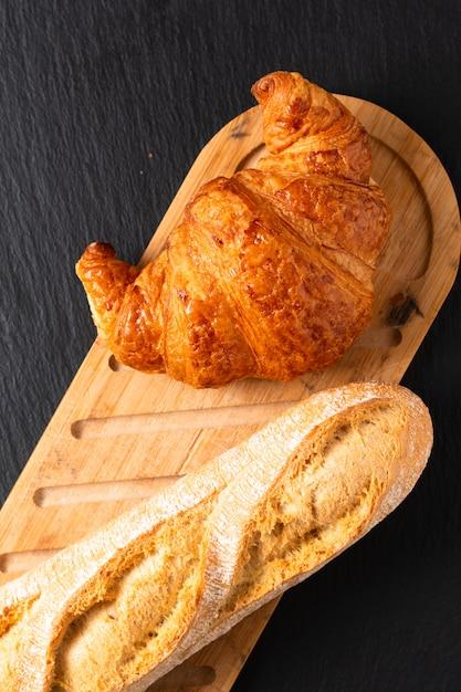 Croissant francese sul bordo dell'ardesia nera con lo spazio della copia Foto Premium