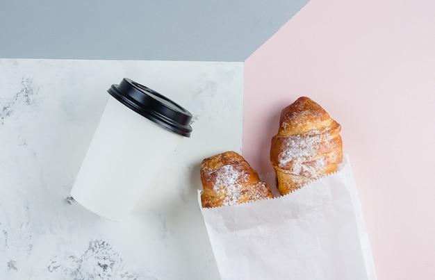 Croissant freschi con caffè per andare in un bicchiere di carta su sfondo tricolore. portare via la colazione. Foto Premium