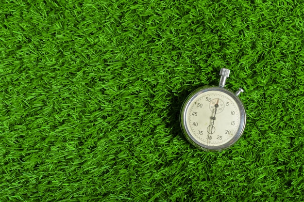 Cronometro d'argento su erba verde Foto Premium
