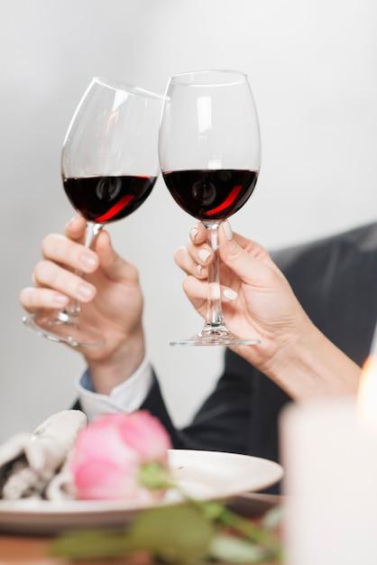 Crop coppia tintinnio con bicchieri da vino Foto Gratuite
