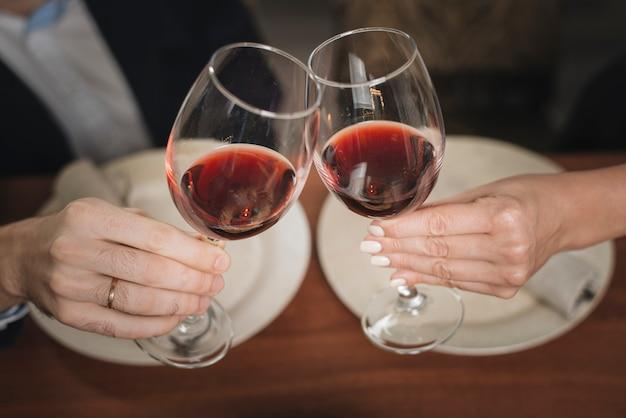 Crop coppia tintinnio con vino Foto Gratuite
