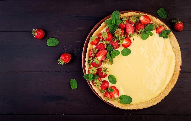 Crostata con fragole e panna montata decorata con foglie di menta. vista dall'alto Foto Premium