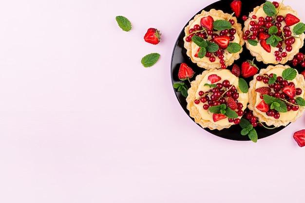 Crostate con fragole, ribes e panna montata decorate con foglie di menta Foto Gratuite