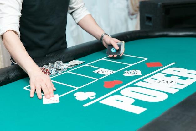 Croupier al tavolo da poker del casinò. fiches e carte in tavola. Foto Premium