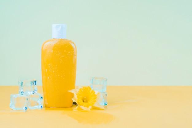 Cubetti di ghiaccio di cristallo con il fiore del narciso e la bottiglia gialla della lozione della protezione solare contro il contesto verde Foto Gratuite