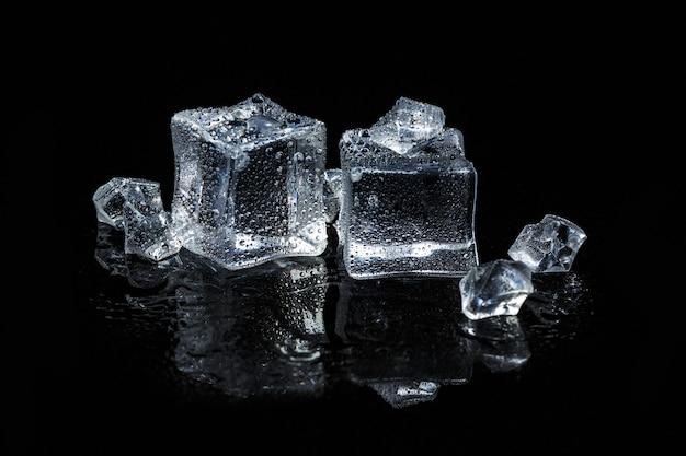 Cubetti di ghiaccio su fondo di vetro isolato nero Foto Premium