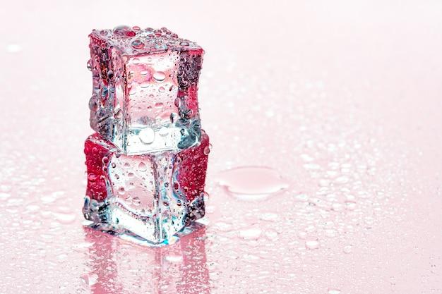 Cubetti di ghiaccio su sfondo rosa Foto Premium
