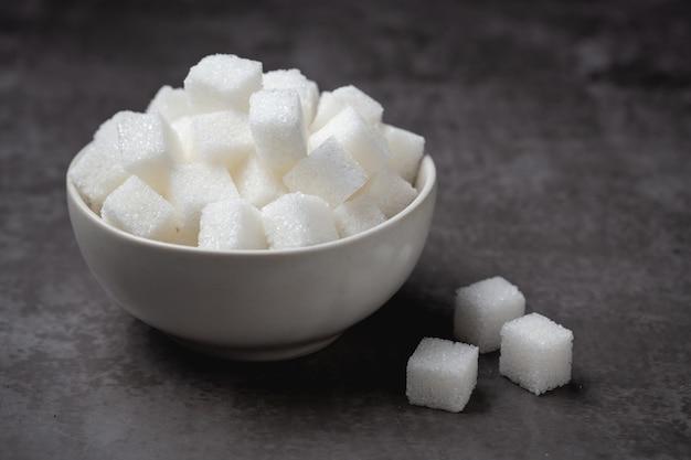 Cubi dello zucchero bianco in ciotola sulla tavola. Foto Gratuite