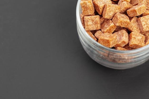 Cubi dello zucchero bruno su fondo grigio Foto Premium