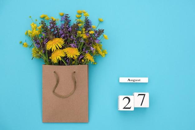 Cubi di legno calendario 27 agosto e campo fiori rustici colorati nel pacchetto del mestiere sul blu Foto Premium