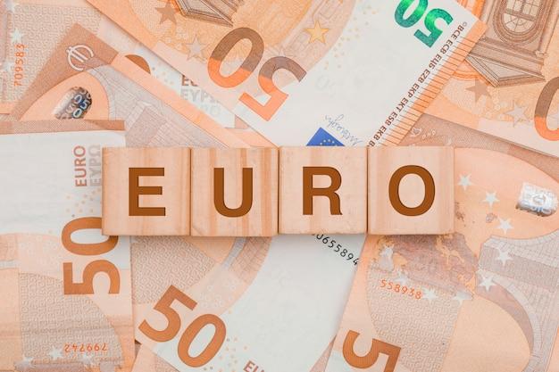 Cubi di legno con la parola euro sul tavolo delle banconote. Foto Gratuite