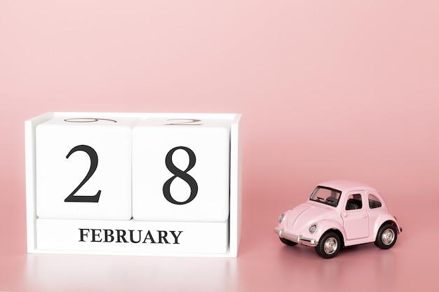 Cubo di legno del primo piano il 28 febbraio. giorno 28 del mese di febbraio, calendario su una rosa con auto retrò. Foto Premium