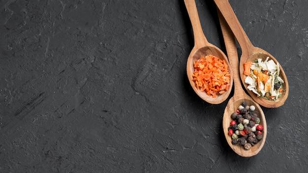 Cucchiai di legno pieni di spezie su sfondo nero Foto Gratuite