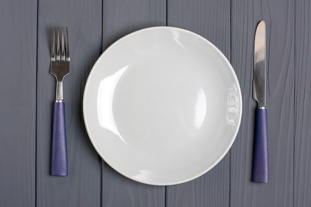 Cucchiaio blu scuro, forchetta, coltello, piatto grigio su un tavolo di legno grigio Foto Premium