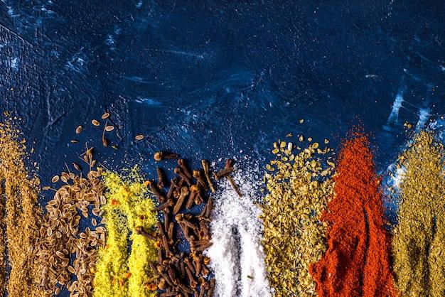 Cucchiaio d'annata dei semi di cumino della paprica del sale della paprica del sale dello zenzero della cannella dello zenzero del pepe della curcuma varie spezie sulla tavola. vista dall'alto spezie indiane Foto Premium