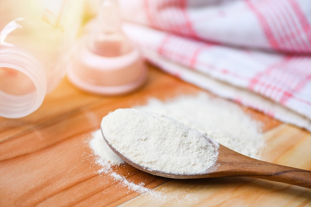 Cucchiaio di latte in polvere con latte bottiglia bambino sul tavolo di legno Foto Premium