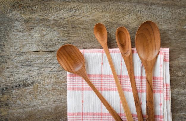 Cucchiaio di legno e set di utensili da cucina cucchiaino da caffè di varie dimensioni sulla tovaglietta sul tavolo da pranzo Foto Premium