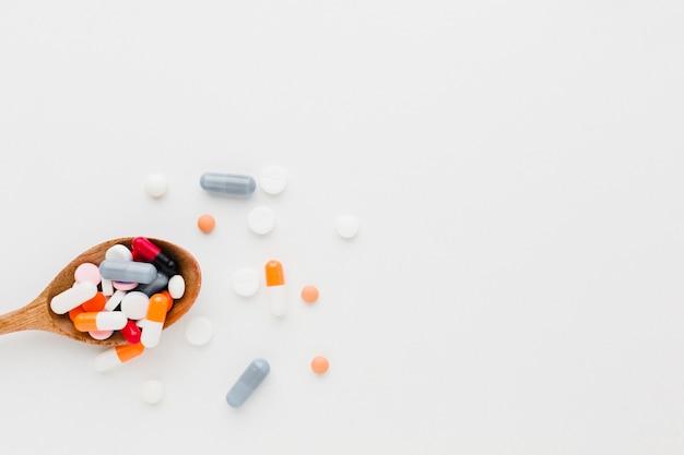 Cucchiaio di legno vista dall'alto pieno di pillole Foto Gratuite