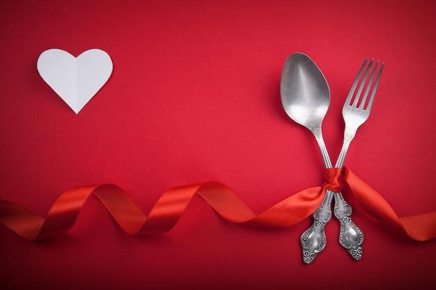 Cucchiaio e forchetta d'annata con una burocrazia e un cuore bianco per il san valentino. Foto Premium