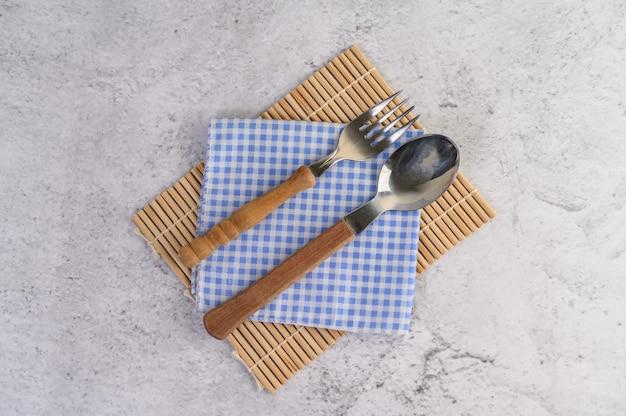 Cucchiaio e forchetta posizionati su fazzoletti bianchi e blu Foto Gratuite