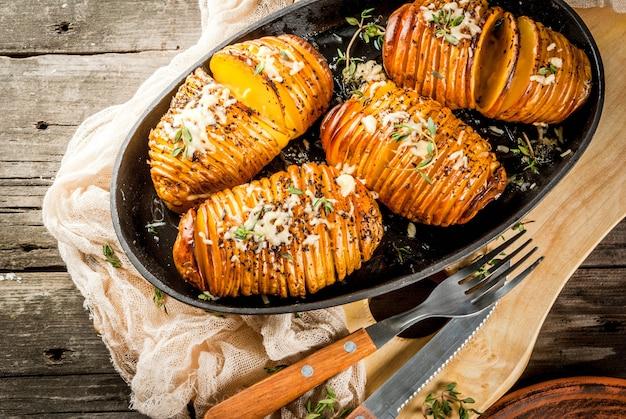 Cucina casalinga tradizionale americana. la dieta vegana patata hasselback fatta in casa con erbe fresche e formaggio. sul vecchio tavolo di legno, copia spazio Foto Premium