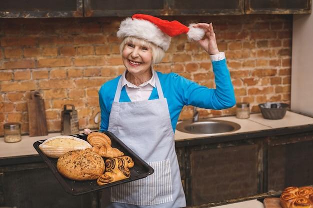 Cucina di capodanno. il ritratto della donna invecchiata senior attraente sta cucinando sulla cucina. nonna che produce cottura saporita di natale. Foto Premium