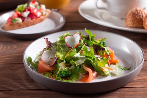 Cucina mediterranea insalata. fette di salmone con insalata di verdure fresche su un piatto. Foto Premium