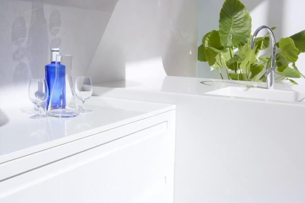 Cucina moderna bianca, bottiglia d'acqua blu e piante Foto Premium