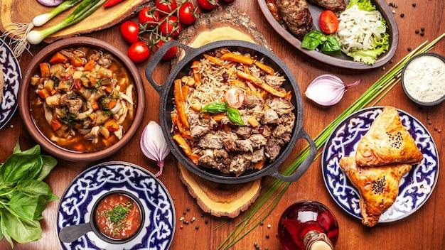 Cucina orientale tradizionale uzbeka. tavolo della famiglia uzbeka di diversi piatti per le vacanze di capodanno. Foto Premium