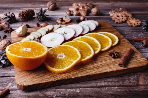 Cucina vin brulè arance, mele e specie si trovano sul tavolo di legno Foto Gratuite