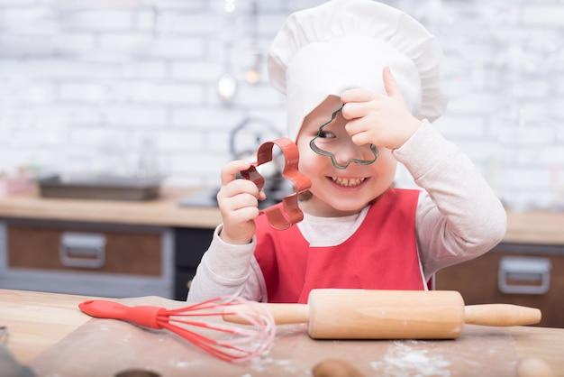 Cucinare è divertente. piccola ragazza del cuoco unico che gioca con la farina. ragazza che lavora alla pasta con il mattarello per produrre i biscotti del pan di zenzero. Foto Premium