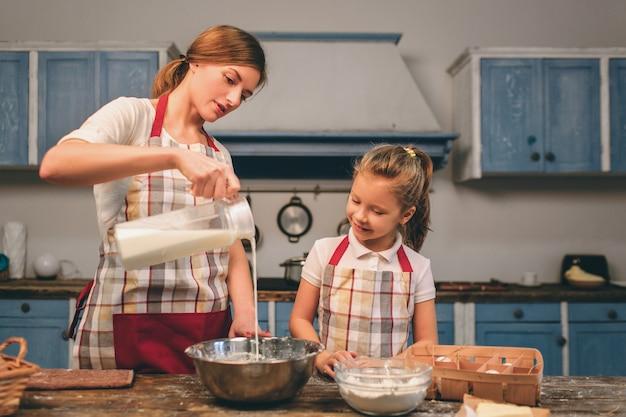 Cucinare torte fatte in casa. la famiglia amorosa felice sta preparando insieme il forno. la ragazza della figlia del bambino e della madre sta cucinando i biscotti e si sta divertendo nella cucina. latte per pasta, ingredienti in una ciotola Foto Premium