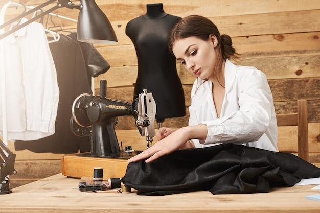 Cucire non è solo lavoro, è talento. designer creativo che lavora con la macchina da cucire sotto la sua nuova linea di abbigliamento, concentrandosi e sforzandosi di renderlo fantastico mentre si trova nel suo laboratorio Foto Gratuite