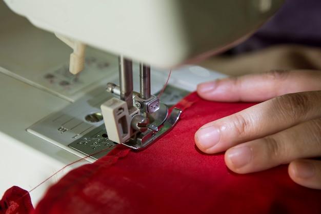 Cucitrice della donna che lavora facendo i vestiti su una macchina per cucire. Foto Premium