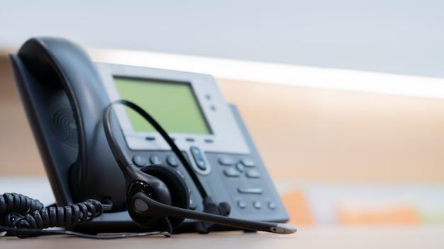 Cuffia con dispositivi telefonici alla scrivania per il concetto di supporto del servizio clienti Foto Premium