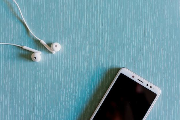 Cuffie bianche e smartphone vista dall'alto Foto Premium