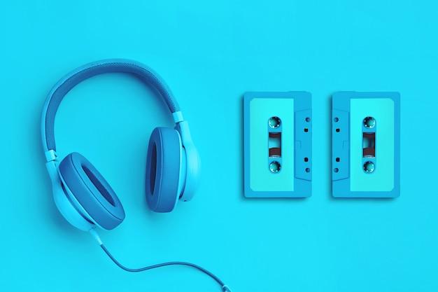 Cuffie blu con audiocassetta su uno sfondo colorato Foto Premium