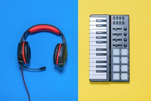Cuffie con microfono e fili e mixer di musica sul tavolo giallo e blu. la vista dall'alto. Foto Premium