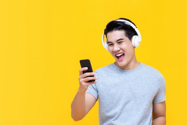 Cuffie d'uso sorridenti dell'uomo asiatico che ascoltano la musica dallo smartphone Foto Premium