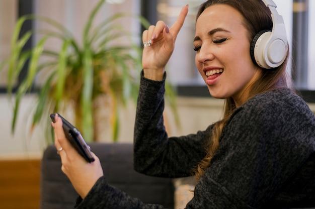 Cuffie da portare della donna che esaminano telefono e che cantano Foto Gratuite