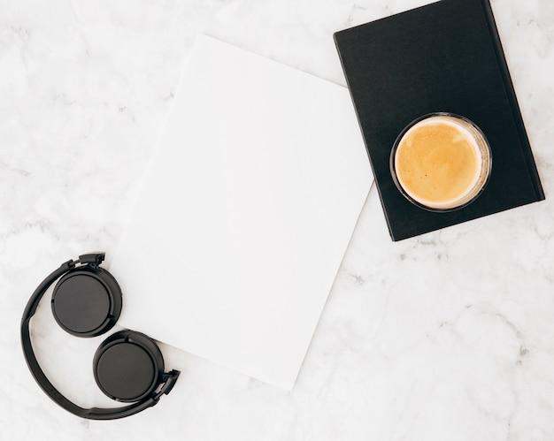 Cuffie; foglio bianco; diario e caffè in vetro su marmo strutturato su sfondo bianco Foto Gratuite